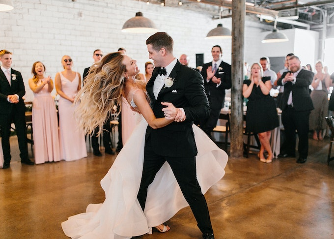 photo of a bridesmaid and groomsman in a black tuxedo dancing during a wedding ceremony