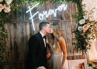 photo of a young bride and groom kissing under a neon sign that says forever