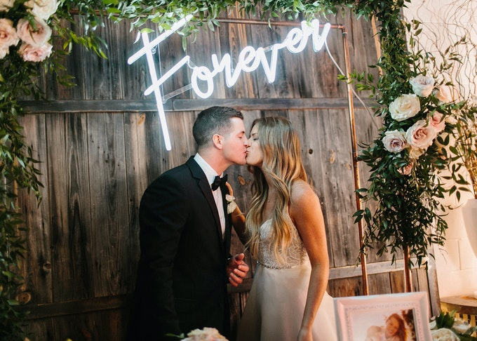 photo of a young bride and groom in a black tuxedo kissing under a neon sign that says forever
