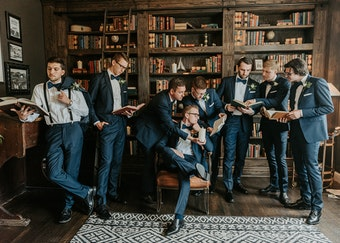 posed photo of groomsmen in a library wearing navy tuxedos while reading books