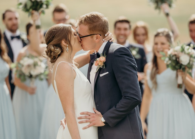 photo of a blonde groom kissing his bride during a wedding ceremony