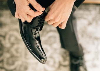photo of a man wearing a nice watch while tying his glossy black tuxedo shoes