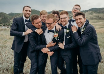 photo of a groom and his groomsmen laughing candidly while wearing navy tuxedos