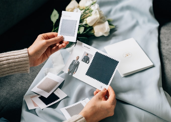 photo of a woman's hands holding suit color swatches comparing to a bridesmaid dress