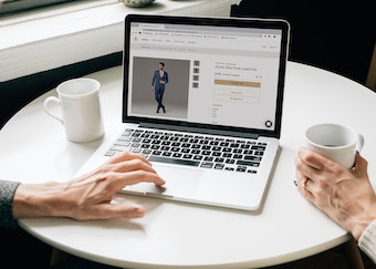 photo of two people's hands while browsing generation tux website drinking coffee