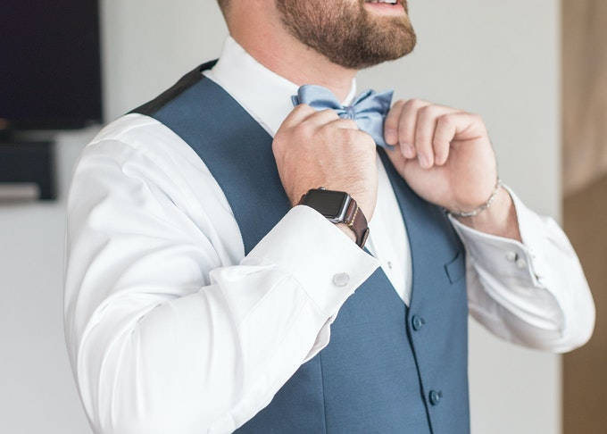 photo of a man straightening his blue bowtie while wearing a blue tuxedo