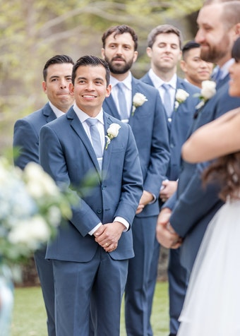 photo of young groomsmen wearing blue suits and smiling during a wedding