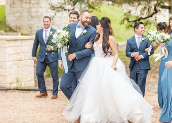 candid photo of a groom and bride walking together while smiling at each other