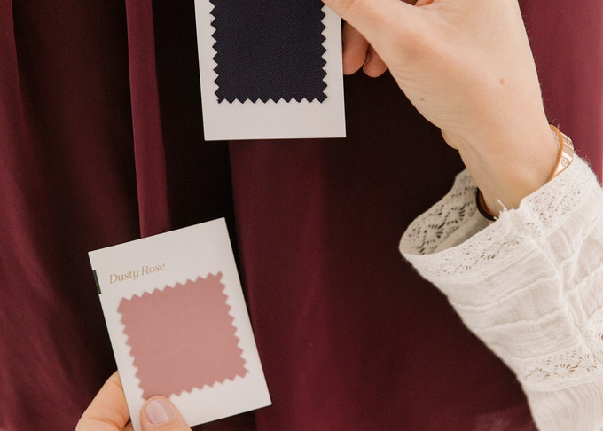 photo of a woman's hands holding pink and purple suit swatches next to bridesmaid dress