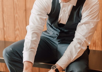photo of a man putting on his shoes while wearing a grey tuxedo