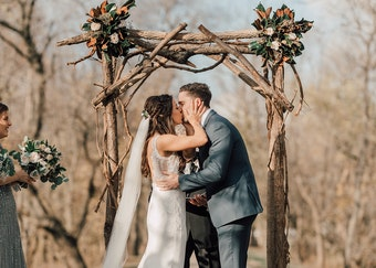 photo of a bride and groom kissing underneath a wooden arch while outdoors
