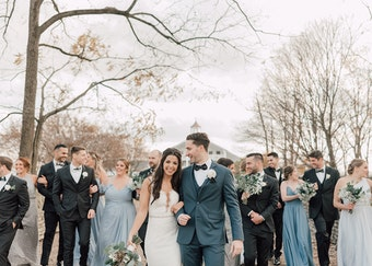 photo of a wedding party and a bride and groom posing outdoors during the winter