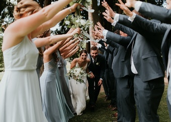 photo of groomsmen and bridesmaids making a tunnel with their arms