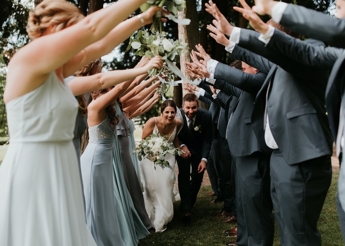 photo of groomsmen in gray suits and bridesmaids making a tunnel with their arms