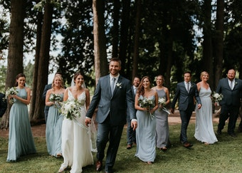 photo of a wedding party walking together in the woods