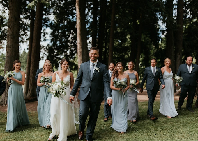 photo of a wedding party with groom and groomsmen wearing blue suits walking together in the woods
