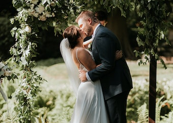 photo of a bride and groom kissing while under an array of white flowers