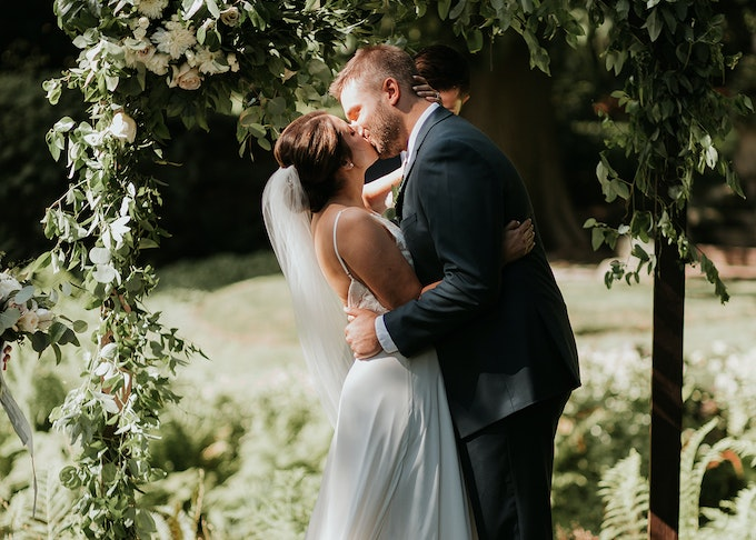 photo of a bride and groom in blue suit kissing while under an arch of greenery