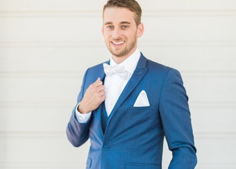 photo of a young groomsman wearing a blue tuxedo while smiling into the camera