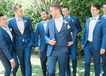 photo of groomsmen and the groom wearing blue tuxedos while outdoors