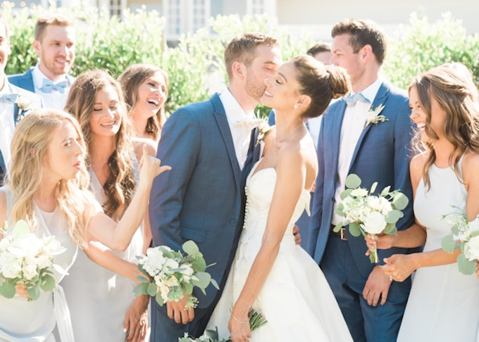 photo of a wedding party and a newly married couple kissing
