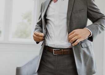photo of a man adjusting the coat on his grey suit
