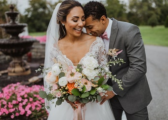photo of a young groom and bride embracing during a wedding with flower bouquet