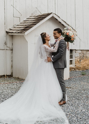 photo of a young bride and groom in wedding attire embracing outdoors behind a house