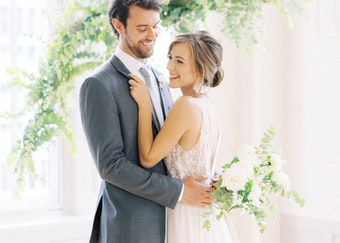 photo of young couple hugging during a wedding with floral decor in the background