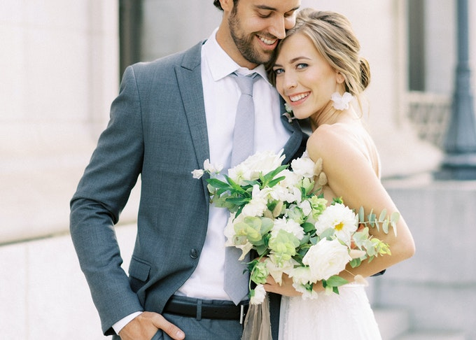photo of a young groom and bride posing during wedding while smiling into the camera