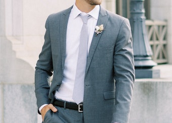photo of a man's torso wearing a slate blue suit with a light blue tie and white shirt