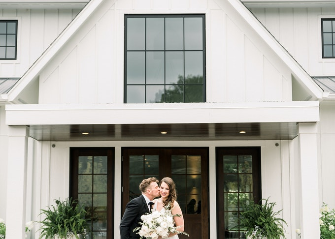 photo of a young groom kissing his bride on the cheek in front of a white house