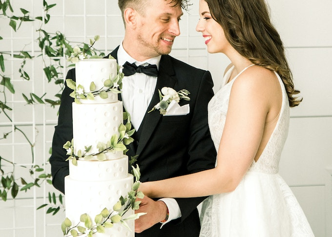 photo of a young groom and bride posing and smiling next to a wedding cake