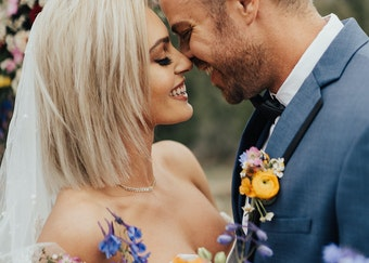 photo of a groom and blonde bride smiling and embracing during wedding ceremony