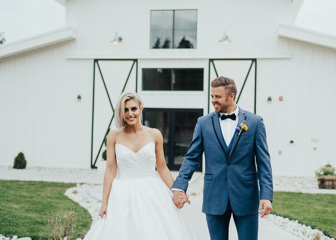photo of a bride and groom in a blue tuxedo holding hands