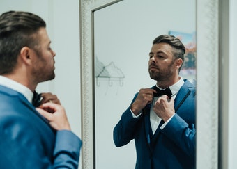 photo of a man wearing a blue tuxedo adjusting his bowtie in the mirror