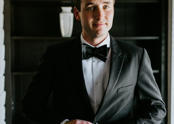 photo of a man closing the button on his black tuxedo wearing black bowtie