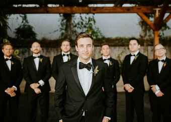 up-close photo of a groom with groomsmen in the background wearing black tuxedos