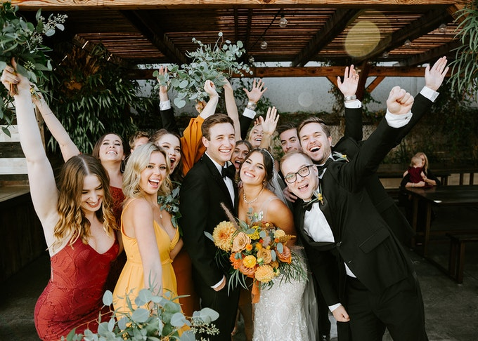 photo of a wedding party with colorful dresses posing with bride and groom