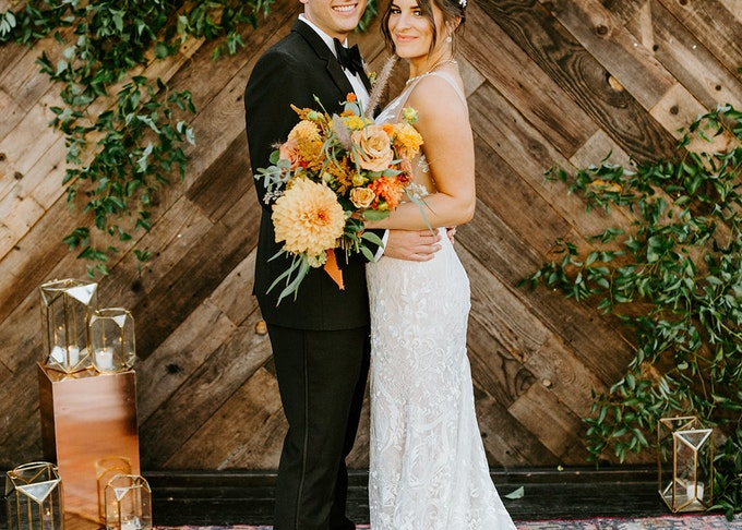 photo of a young groom and bride posing outdoors on a red carpet with orange flowers