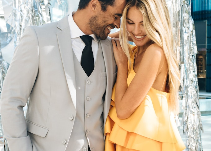 bearded guy in a Menguin cement grey suit and vest with his date
