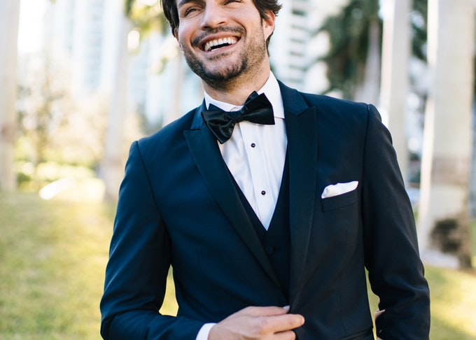 Smiling guy wearing a Menguin black tuxedo with matching vest