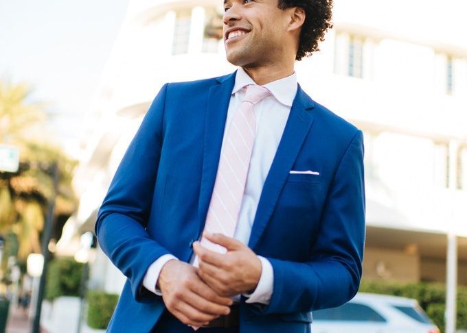 Man outside in blue Menguin suit with tie and pocket square