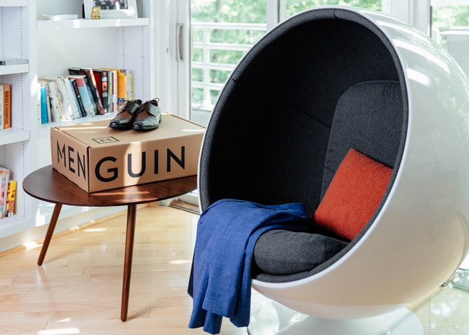 Blue Menguin suit laid out on a modern chair in living room