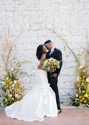 wedding bride and groom standing outside in front of flowers