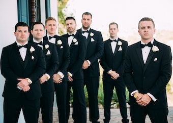 groom and groomsmen posing for a picture outside in black Menguin tuxedos