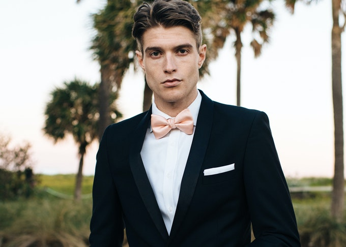 guy in a black Menguin tux featuring a white pocket square and bowtie standing outside below palm trees