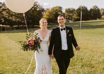 groom in a black Menguin tuxedo with black bowtie walking outdoors with his bride in a white wedding dress holding flowers and giant balloons