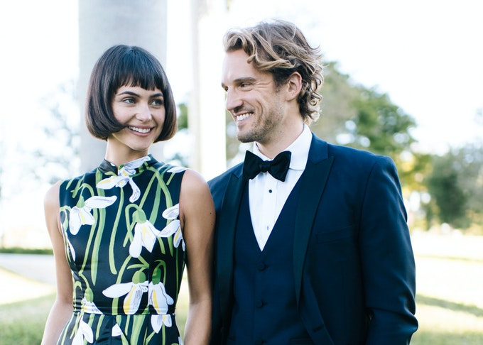 guy wearing a midnight blue tuxedo standing next to a female in a floral romper
