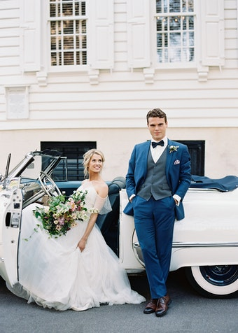 groom in a blue wedding suit with a gray vest standing outside of an old white car with his bride gazing at him